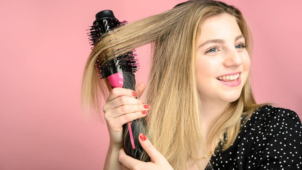 Woman doing hair with black and pink hair tool, against a pink background