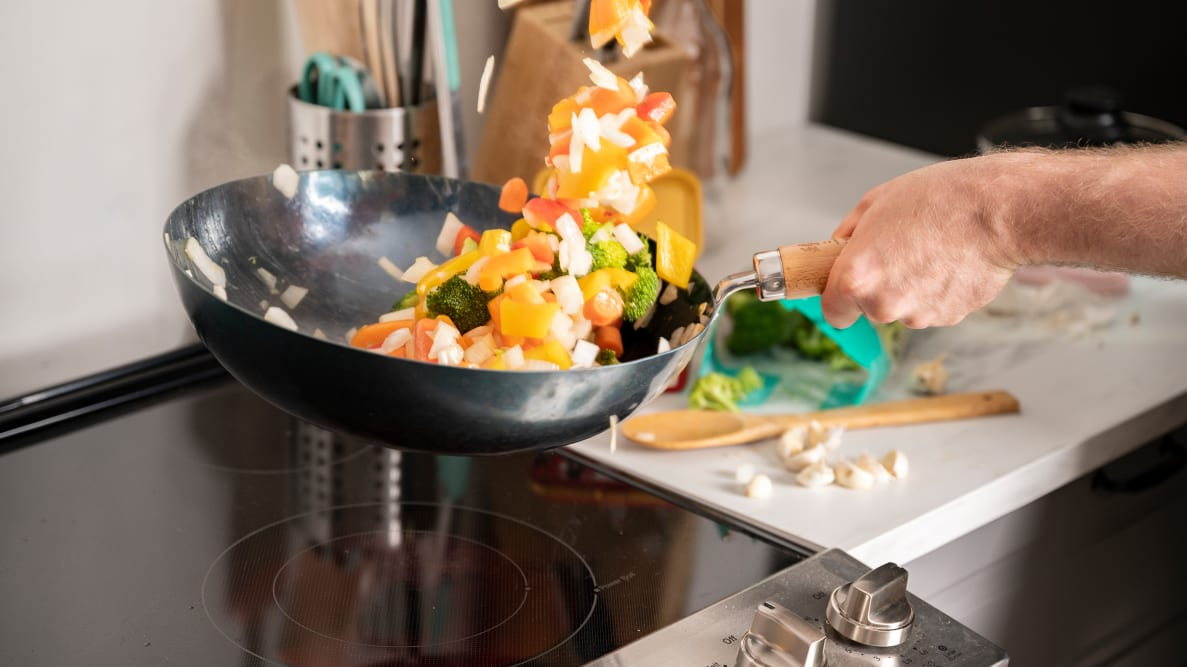 A person is stir frying a medley of vegetables in a carbon steel wok over an electric cooktop.