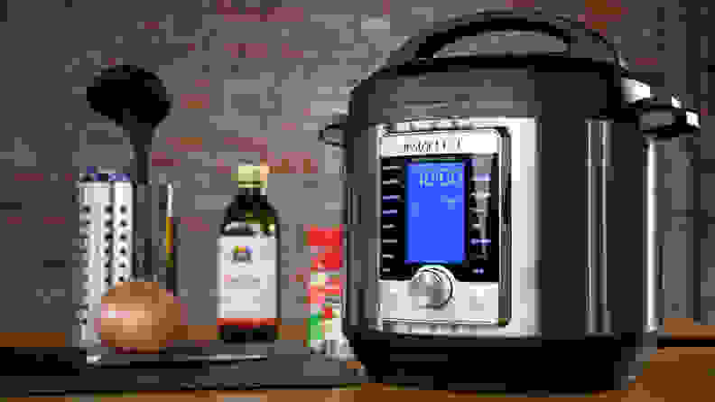 An Instant Pot shown besides some cooking utensils, an onion, an some sauces.
