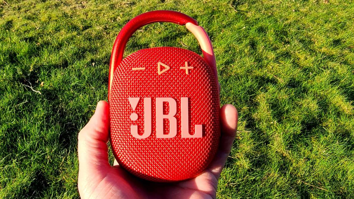 JBL Clip 4 red Bluetooth speaker in-hand before green grass
