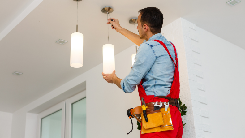 Electrician installing light fixture on ceiling.