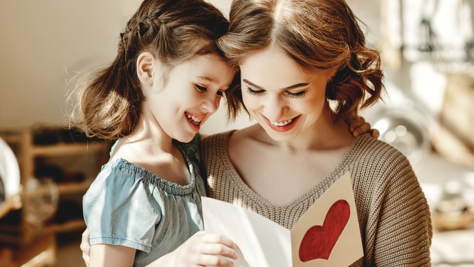 A mother and daughter read a card together