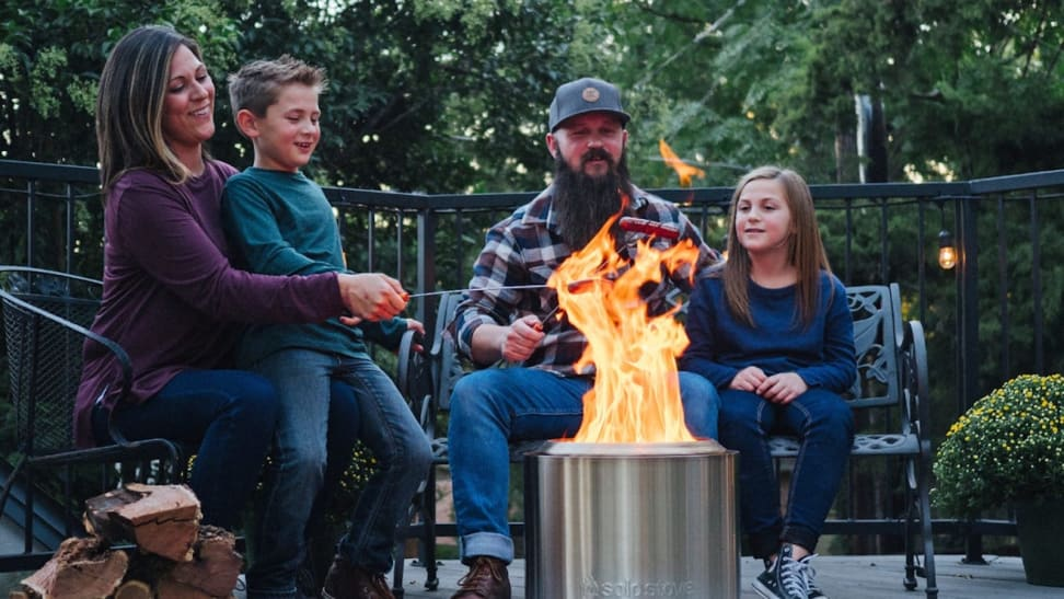 A family sits around their Solo Stove fire pit.