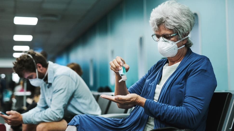 An older woman applies hand sanitizer in an airport waiting area