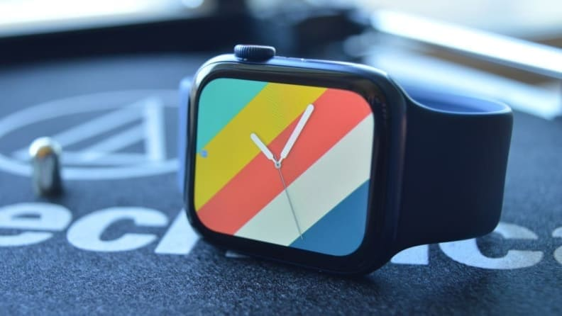 An Apple Watch Series 6 with a brightly colored rainbow watch face.