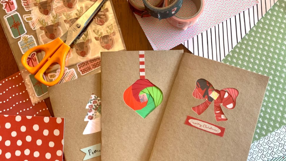 Homemade Christmas cards laying on top of decorative paper, stickers, washi tape, scissors