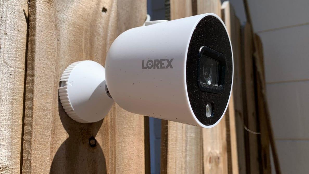 The Lorex Smart Indoor/Outdoor 1080p WiFi Camera hangs on a wood fence.