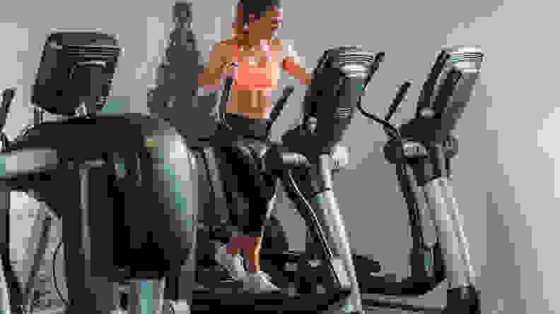 A woman using the elliptical at the gym.