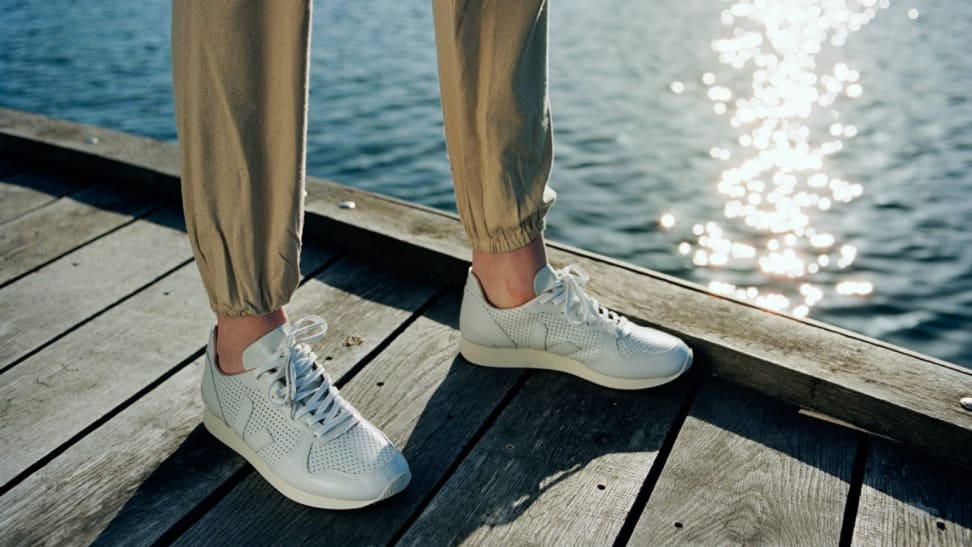 Someone wearing sneakers on a dock.