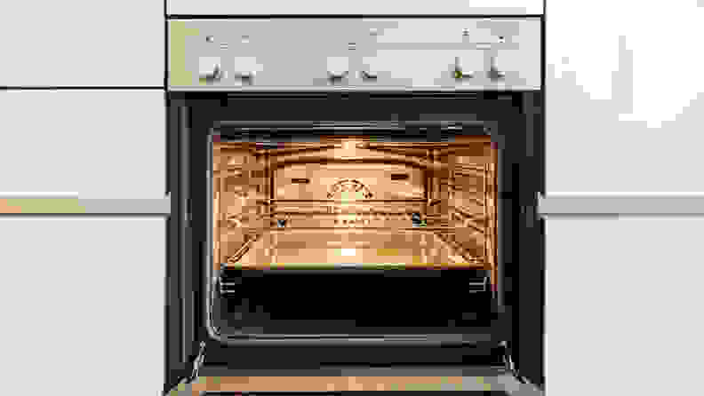 A stainless-steel oven with the interior light turned on.