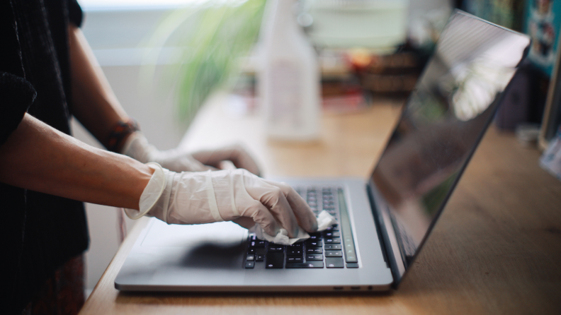 A woman sanitizes her laptop surface against viruses and germs.