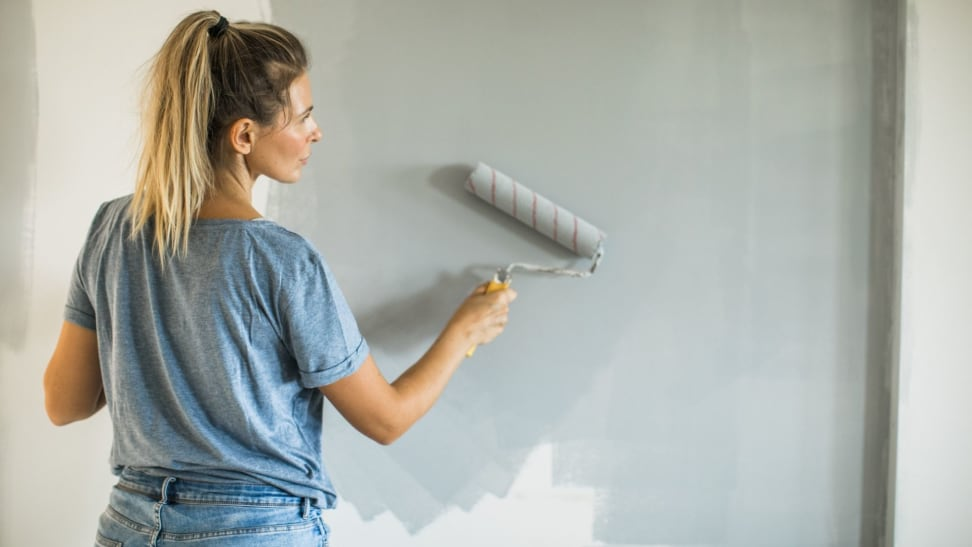 Woman painting wall in home