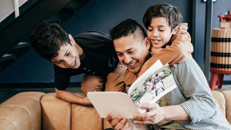 A parent shows children a family photo album.
