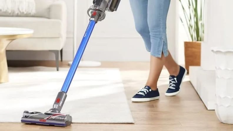 A person vacuums a carpet and wood floor with a Dyson vacuum.