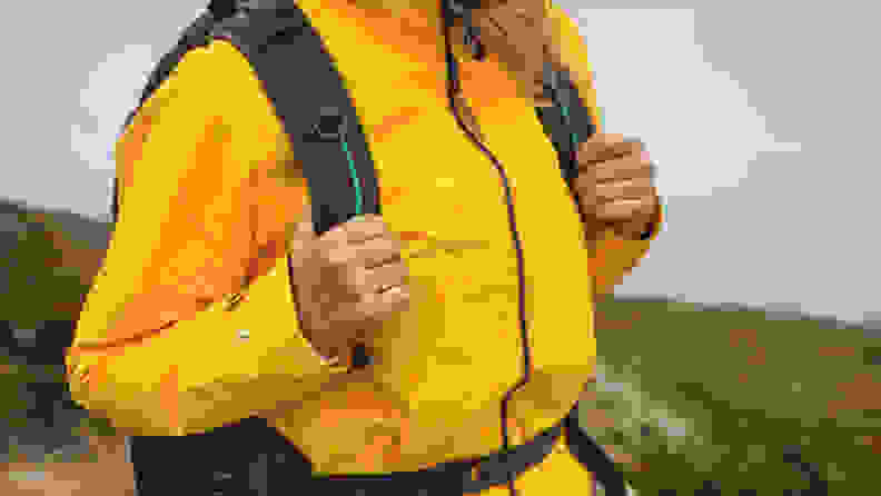 A woman walking in mountains and wearing a yellow jacket.