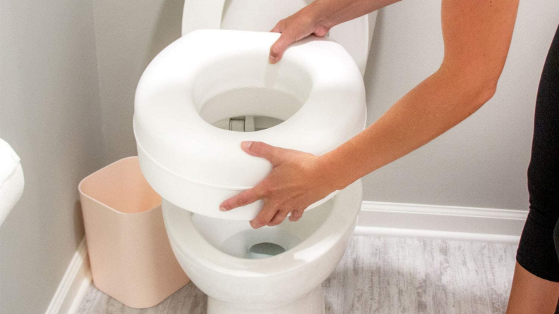 A person installs an elevated toilet seat.