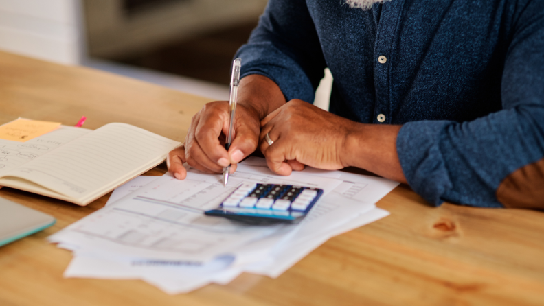 Man holds pen while using calculator to do financial planning.