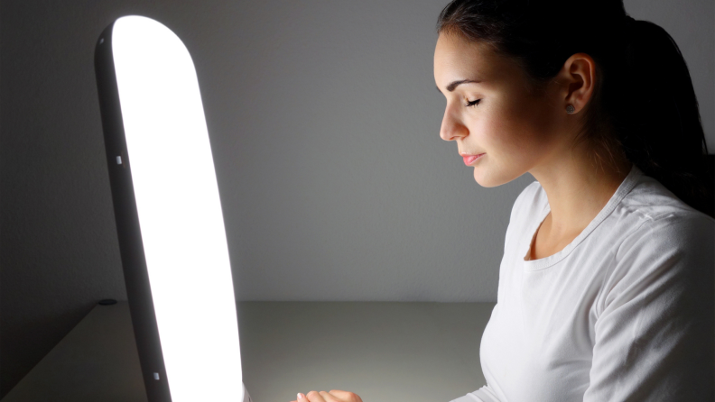 Person sits in front of light therapy lamp with eyes shut to improve mood.