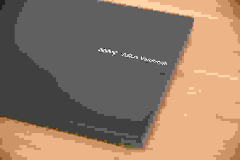 A close-up of a logo on top of a closed laptop