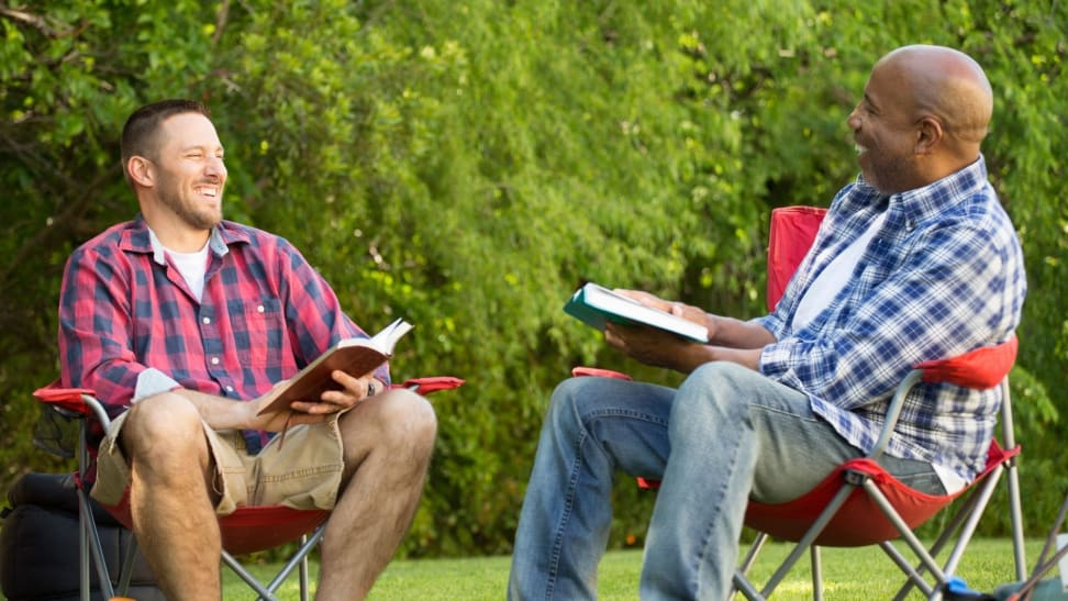 Two men talking and laughing over books while camping.