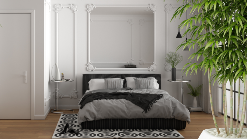 A minimalistic bedroom surrounded by green plants and a massive mirror above a bed.