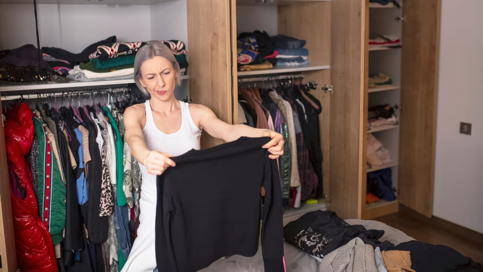 Woman inspecting black sweater in her closet.