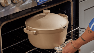 A person is pulling an oven rack, which has the Perfect Pot in gray color on it.