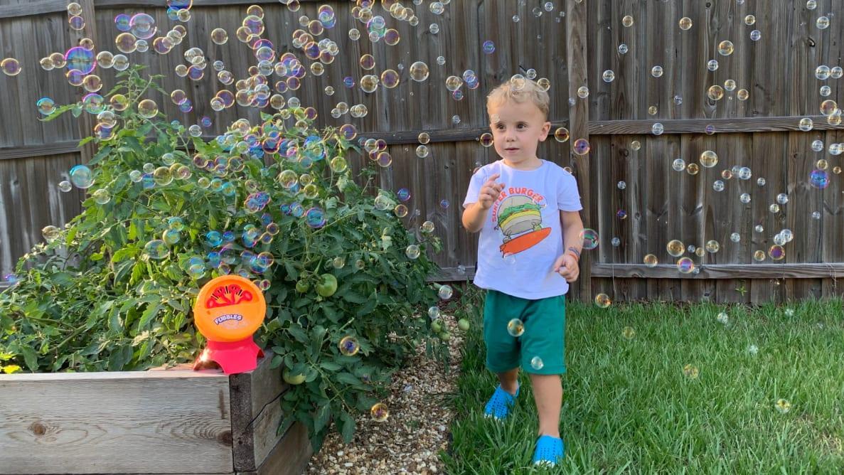 A toddler runs through bubbles outside
