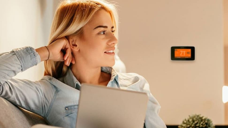 A woman sits down with a Sensi smart thermostat pictured on the wall behind her.