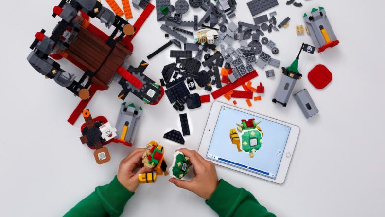 A child's hands build a Lego set over an app shown on an iPad.