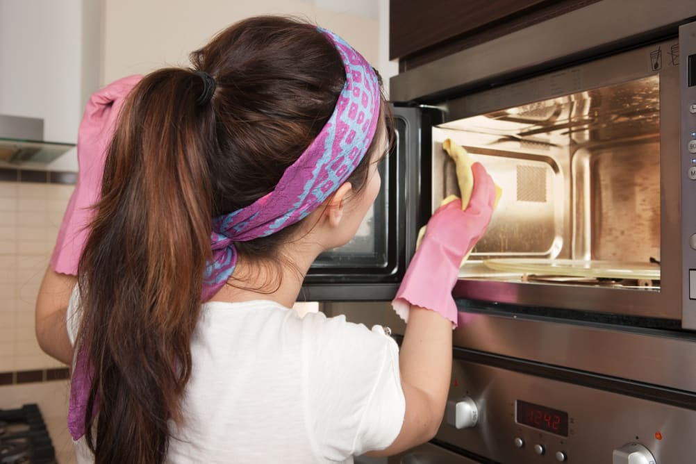 Woman cleaning kitchen appliances in her home