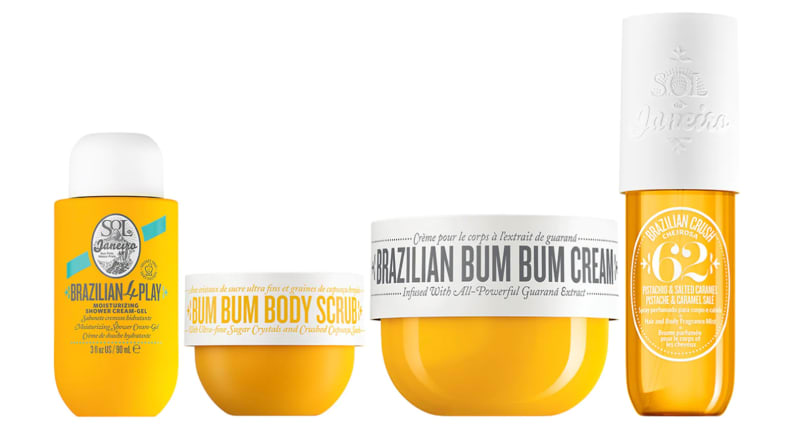 A bottle of body wash, a tub of body scrub, a tub of moisturizer, and a body spray sit side by side in yellow containers.