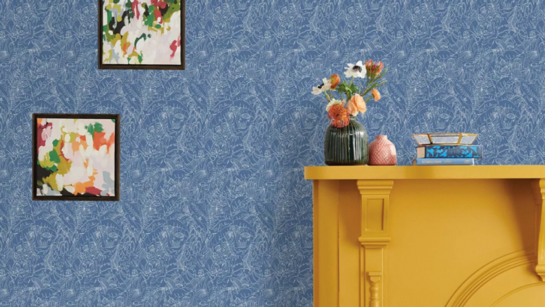 A light blue wallpaper is pasted on the walls. Hanging on the wall are two picture frames. There is a mustard yellow fireplace on the right side of the photo.