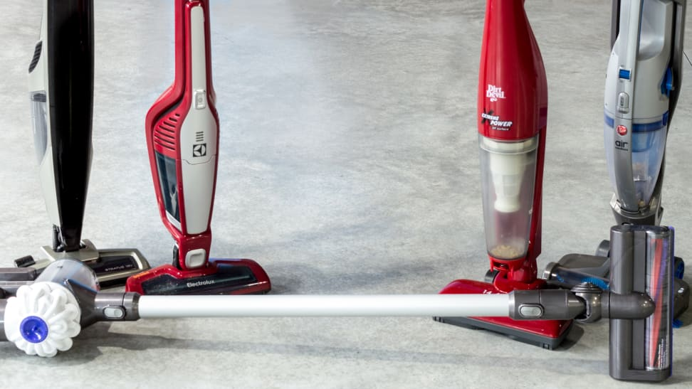 Four cordless vacuums standing side by side and one lying on its side on a grey concrete floor.