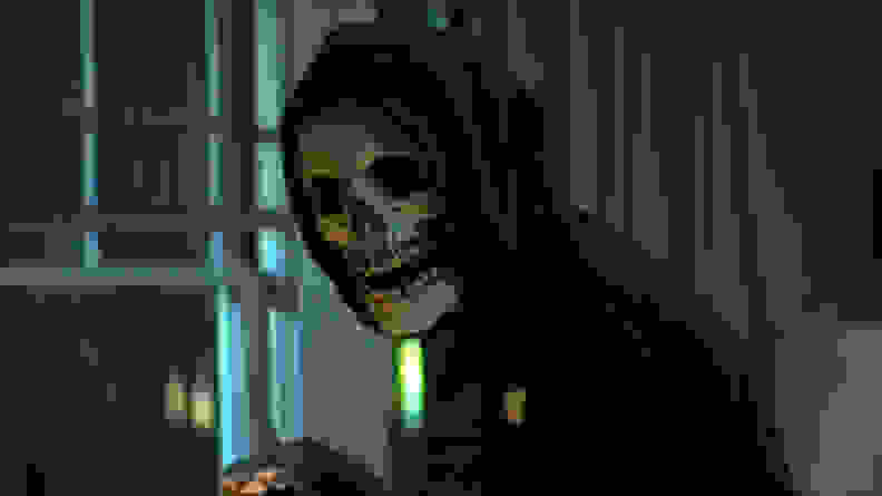 A person in a skeleton mask against a window, in a scene from