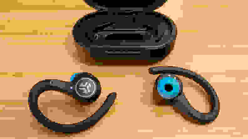 A pair of JLab Epic Air Sport earbuds and charging case on a brown table.