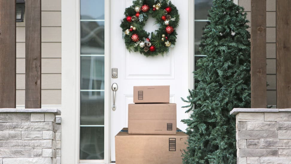 Stack of boxes sitting on a front porch decorated for the holidays.