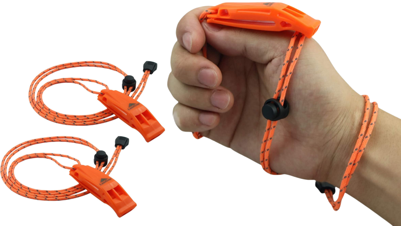 A person holds a bright orange emergency whistle.