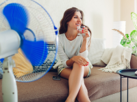 A blue fan spins while a woman sits on couch drinking water