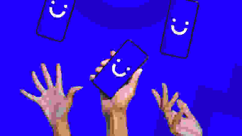 Hands holding phones with smiley faces on blue background