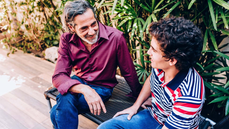 A dad talks to his teenage son as they sit on an outdoor bench.