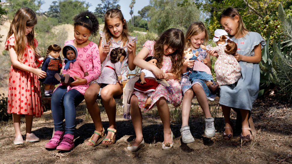 A group of six girls sitting on a bench each holding a different American Girl doll