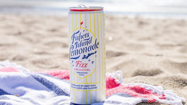 A can of spiked lemonade sits atop a beach towel on a sandy beach.