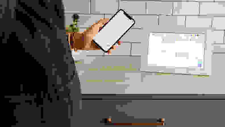 A person holding an iphone standing next to a digital calendar