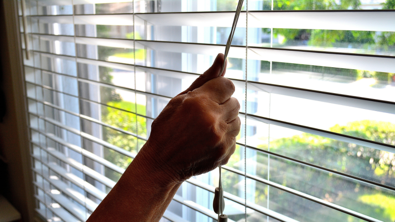 a person holds onto a cord and closes window blinds in front of a window during the day