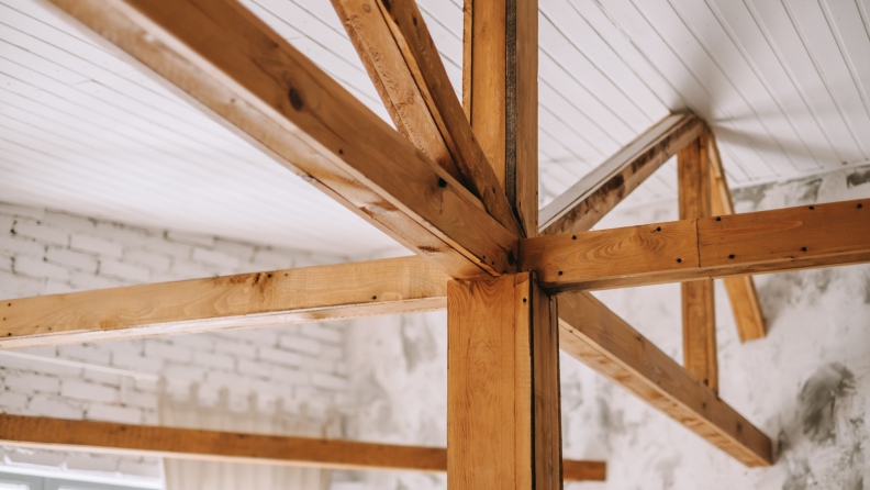 Photo of angular wooden rafters supporting a painted white ceiling.
