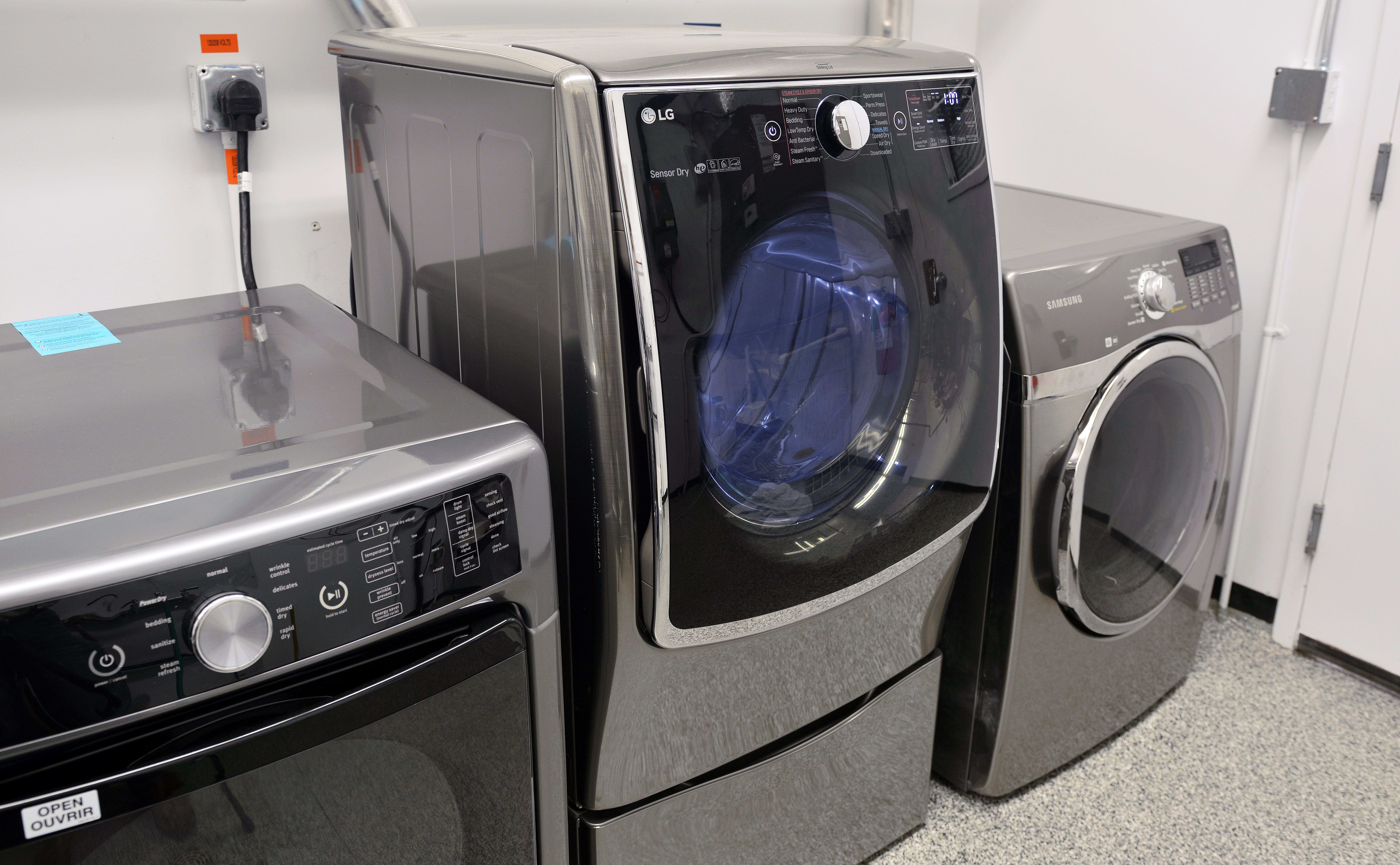 The LG DLEX5000V flanked by two conventional dryers, atop the WDP4V pedestal—which happens to feature a drawer for storage.