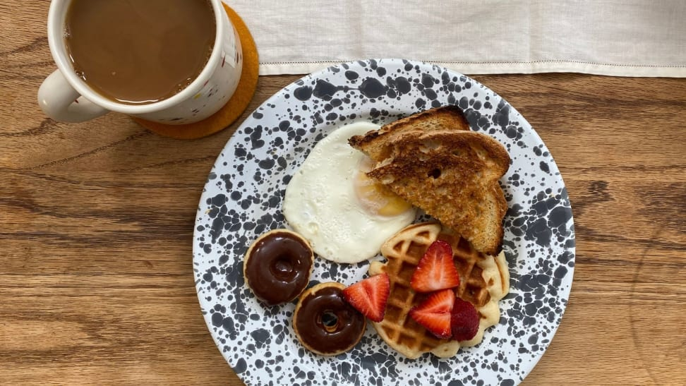 Mini toast, donuts, waffles, and a fried egg on a white and grey speckled plate accompanied by a mug of hot coffee.