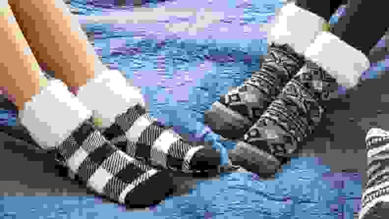 Two people sit down wearing Pudus fuzzy socks.