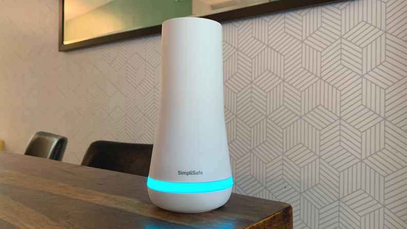 A SimpliSafe home hub sits on a wooden dining room table.